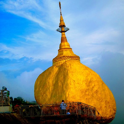 The Golden Rock in Myanmar with a blue sky background