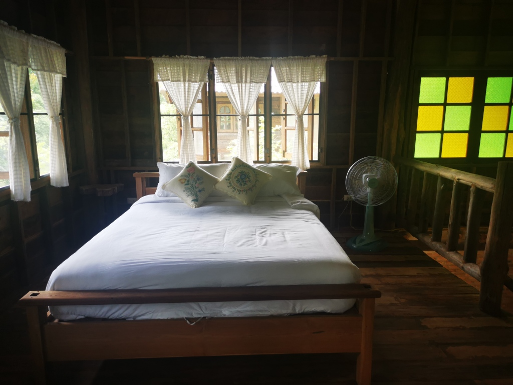 The bed on the upper floor in the house at Take a Walk coffee.